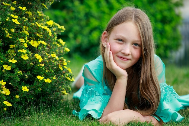 Une fille en robe bleue se trouve sur l'herbe dans le parc