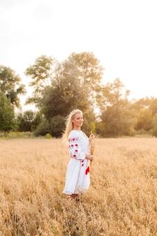 Fille en robe brodée blanche tenant un bouquet d'épillets dans le domaine