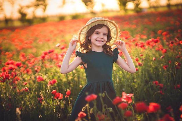 Fille en robe et chapeau de paille en plein air au champ de coquelicots