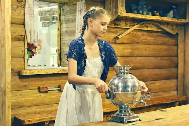 Fille en robe dans une maison en bois avec un samovar