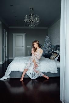 Une fille en robe de dentelle sur un lit