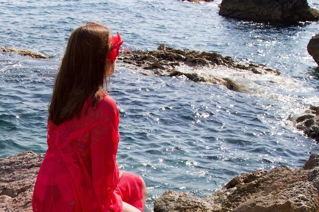 Une fille en robe écarlate au bord de la mer. vent, vagues, plage déserte. des vacances dans le sud
