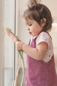 Une fille en robe d'été rose tient une tulipe. un enfant se tient à la fenêtre.