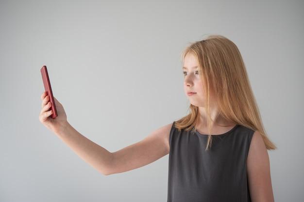 Une fille en robe grise et avec un téléphone sur fond gris prend des photos