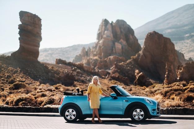 Fille en robe jaune profitant d'un road trip en décapotable à travers une vallée déserte avec des montagnes, îles canaries, ténérife.