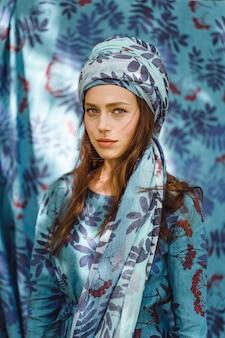Fille en robe en lin. avec une guirlande de fleurs sur sa tête.