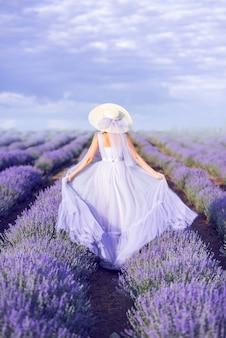 Fille en robe longue court dans un champ de lavande. la mariée à la lavande. photo de l'arrière.