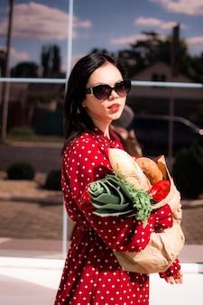 Une fille en robe marche dans la rue en tenant un sac en papier avec des provisions dans ses mains.