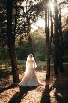 Fille en robe de mariée dans la forêt d'automne sur fond d'arbres sauvages
