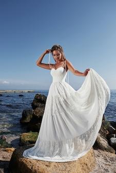 Fille en robe de mariée de luxe posant sur le bord de mer. mariée sur des rochers.