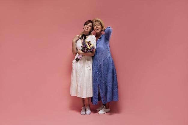 Fille en robe midi blanche et chapeau de paille tenant des fleurs sauvages, souriant et posant avec une femme blonde en vêtements bleus sur fond rose.