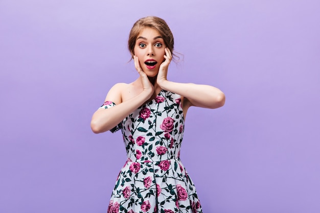 Fille en robe à la mode semble surprise. choqué jeune femme avec des lèvres roses dans des vêtements lumineux à la mode posant sur fond isolé.