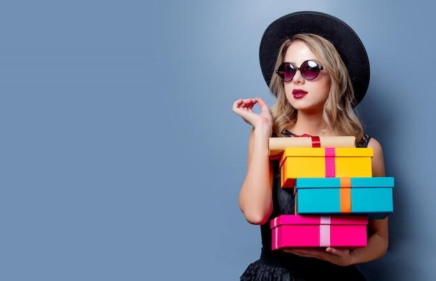Fille en robe noire et chapeau avec des coffrets cadeaux