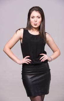 Une fille en robe noire tirait la langue.