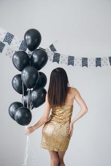 Fille en robe d'or avec des ballons noirs