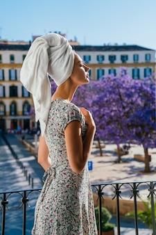 Fille en robe rétro profite du temps sur le balcon. fond de ville européenne