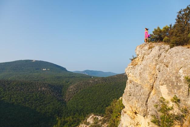 Une fille en robe rose se dresse sur un rocher devant un précipice