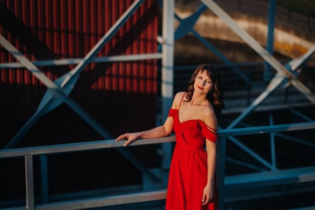Une fille en robe rouge sur un barrage près d'une rivière au coucher du soleil.