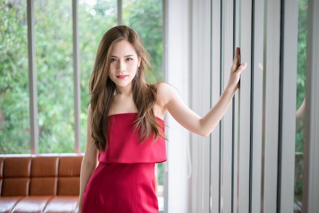 Une fille en robe rouge est debout à côté de la fenêtre.