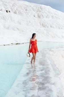 Fille en robe rouge sur travertins blancs, eau
