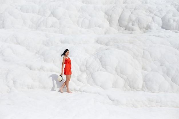 Fille en robe rouge sur travertins blancs