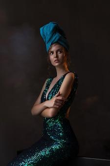 Fille en robe vert-bleu brillant et serviette sur la tête