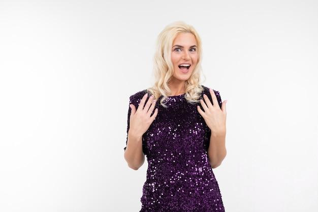 Fille en robe violette est surprise de l'actualité sur un fond de studio blanc