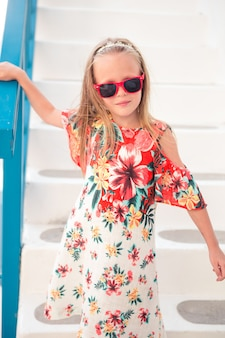 Fille en robes blanches s'amuser à l'extérieur dans les rues de mykonos