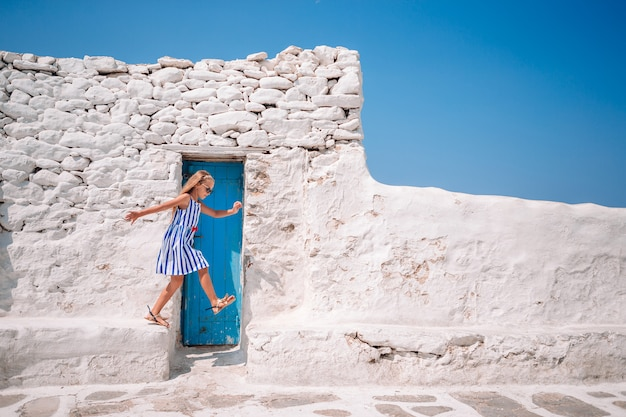 Fille en robes bleues s'amusant en plein air dans les rues de mykonos