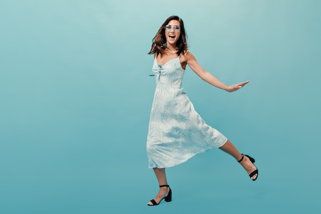 Fille en robes midi et sandales sautant sur fond bleu