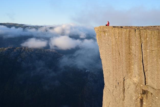Fille sur le rocher preikestolen, norvège