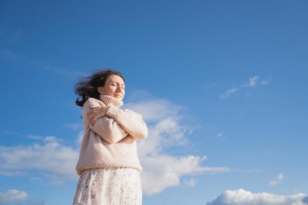 Une fille romantique dans un pull chaud se serre dans ses bras la brune ferma les yeux rêveusement