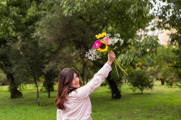 Fille romantique avec des fleurs dans un parc verdoyant
