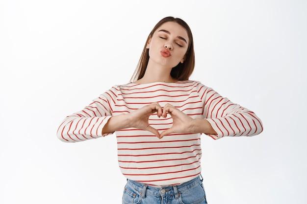 Une fille romantique montre le coeur que je t'aime signe et embrasse, des lèvres plissées pour un baiser aérien, exprime de la tendresse et de l'affection, de la sympathie, comme quelqu'un, debout sur un mur blanc