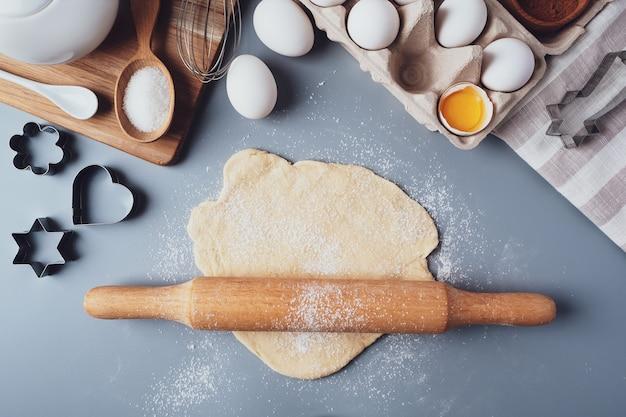 La fille roule la pâte avec un rouleau à pâtisserie en bois pour faire des cupcakes ou des biscuits.