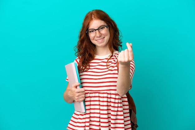 Fille rousse adolescente étudiante isolée sur fond bleu faisant un geste d'argent