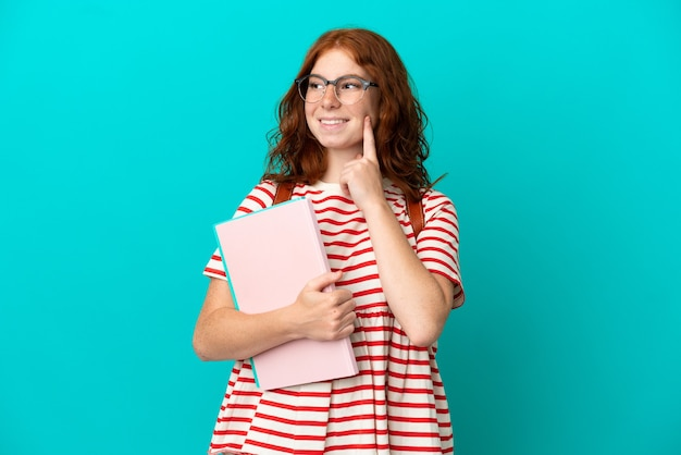 Fille rousse adolescente étudiante isolée sur fond bleu pensant à une idée tout en levant les yeux