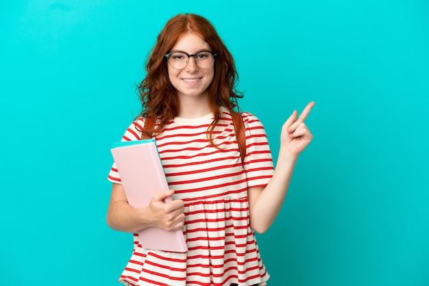 Fille rousse adolescente étudiante isolée sur fond bleu, pointant le doigt sur le côté