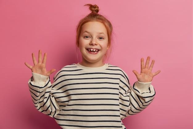Une fille rousse amusante et amusante lève les deux paumes, sourit agréablement, a des dents manquantes, porte un pull rayé, pose contre un mur pastel rose, a une expression insouciante. concept de l'enfance
