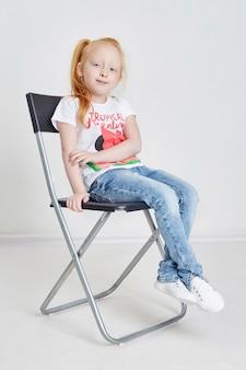 Fille rousse assise sur la chaise du directeur