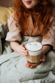 Fille rousse au lit avec une tasse de café avec de la mousse de lait.