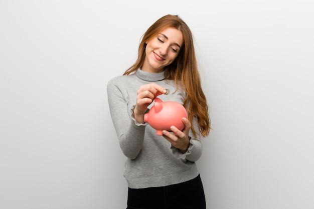 Fille rousse au mur blanc prenant une tirelire et heureuse car elle est pleine