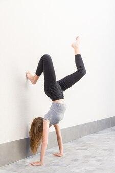 Fille rousse aux cheveux longs faisant un poirier avec les jambes pliées, l'un appuyé sur le mur vêtu d'un pantalon noir et d'un t-shirt gris sur un mur léger