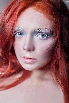 Fille rousse aux cheveux longs, un visage couvert de neige avec du givre. sourcils et cils blancs en gel, une branche d'arbre recouverte de neige. reine des neiges et hiver. visage de femme maquillage hiver, tête rouge