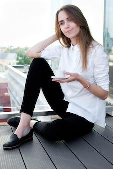 Fille rousse blanche en chemise blanche, boire du café