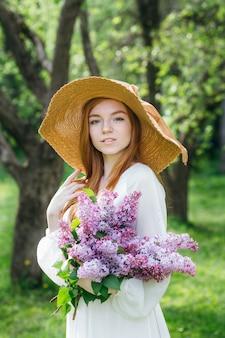 Fille rousse avec un bouquet de lilas dans un jardin de printemps