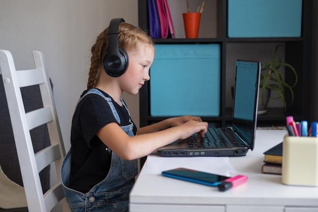 Fille rousse avec un casque à l'aide d'un ordinateur portable tout en étudiant à la maison. retour au concept de l'école.