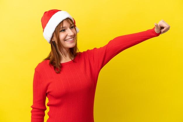 Fille rousse avec chapeau de noël isolé sur fond jaune donnant un geste du pouce vers le haut