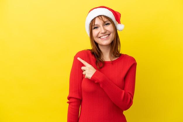 Fille rousse avec chapeau de noël isolé sur fond jaune pointant sur le côté pour présenter un produit