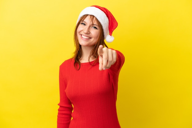Fille rousse avec chapeau de noël isolé sur fond jaune pointant vers l'avant avec une expression heureuse